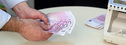Banchiere Counting 500 euro banconote Fotografia Stock