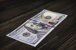 Bancnote de 100 dólares en una tabla de madera Fotografía de archivo libre de regalías