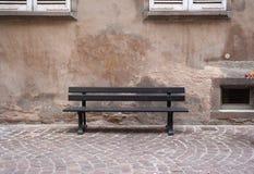 Banco al aire libre del color de Brown oscuro con la pared rústica Imagen de archivo libre de regalías