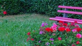 Banco al aire libre del jardín rosado con las flores y los accesorios Fotos de archivo