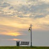 Banco al lado de una luz de calle en la puesta del sol Fotografía de archivo