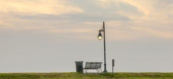 Banco al lado de una luz de calle en la puesta del sol Imagen de archivo libre de regalías