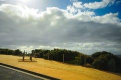 Banco al lado del camino con el cielo azul Foto de archivo