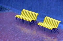 Banco amarillo en la lluvia Foto de archivo libre de regalías