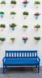 Banco azul com potenciômetros de flor fotografia de stock
