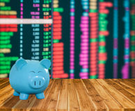 Banco azul del cerdo en el fondo de madera con backgrou del mercado de acción de la falta de definición Fotos de archivo libres de regalías