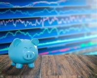 Banco azul do porco no fundo de madeira com o backgrou do mercado de valores de ação do borrão Foto de Stock