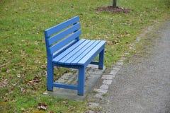 Banco azul en el parque Imágenes de archivo libres de regalías