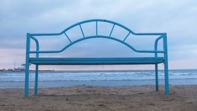 Banco azul en la playa arenosa en la puesta del sol Infraestructura conveniente para relajarse por el mar Onda del mar almacen de metraje de vídeo