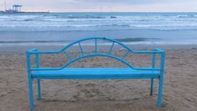 Banco azul en la playa arenosa en la puesta del sol Infraestructura conveniente para relajarse por el mar Onda del mar almacen de video