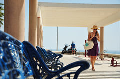 Banco azul no passeio do mar e da mulher Imagens de Stock