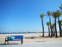 Banco azul pela praia imagem de stock