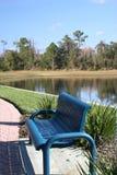 Banco azul por el lago Fotos de archivo