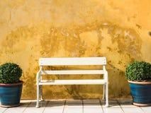 Banco blanco delante de la pared amarilla del vintage Imagen de archivo