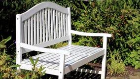 Banco blanco en el jardín, lugar de descanso almacen de video