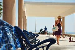 Banco blu alla camminata della donna e del mare Immagini Stock