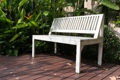 Banco branco no trajeto de madeira no jardim Fotos de Stock