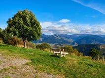 Banco branco que senta-se na parte superior de uma montanha no lado de uma árvore, Font Romeu da rocha do granito fotos de stock
