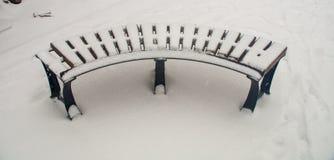 Banco coberto de neve em um parque em Bulgária Pomorie imagens de stock