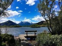 Banco com opinião da montanha e do lago fotografia de stock royalty free