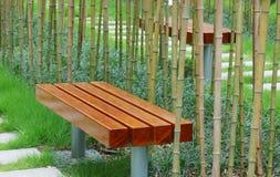 Banco con el bambú alrededor de él imagen de archivo