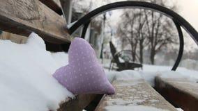 Banco con el corazón en parque del invierno Día de tarjetas del día de San Valentín o idea del invierno del amor almacen de video