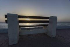 Banco concreto en la salida del sol Imagenes de archivo