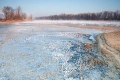 Banco congelado de un río brumoso en madrugada imagen de archivo
