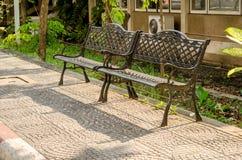 Banco d'acciaio delle vecchie sedie nel giardino Fotografia Stock Libera da Diritti