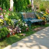 Banco d'annata nel giardino di fiori Fotografie Stock Libere da Diritti