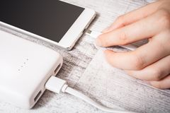 Banco de conexão do poder da mão fêmea com o telefone de PMobile para recarregar a baixa bateria, opinião de ângulo alto fotografia de stock