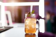 Banco de cristal de la limonada con agrios cortados en una tabla de la barra Imágenes de archivo libres de regalías