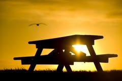 Banco de la comida campestre silueteado contra puesta del sol Imagen de archivo