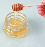 Banco de la miel con el palillo de madera Imagenes de archivo