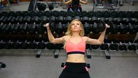 Banco de la mujer joven que presiona con pesas de gimnasia en el gimnasio, el tríceps de trabajo y el pecho metrajes