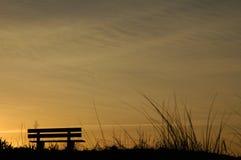 Banco de la playa en la puesta del sol Imagen de archivo