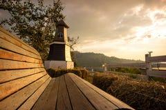 Banco de madeira com fundo do moinho de vento e da montanha no li do por do sol imagem de stock
