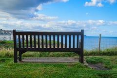 Banco de madeira com o olhar no mar azul Fotos de Stock Royalty Free