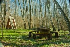 Banco de madeira e tabela na madeira do verão Foto de Stock