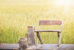 Banco de madeira em um jardim em um fundo do campo do arroz imagens de stock