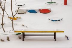 Banco de madeira em uma rua nevado imagens de stock royalty free