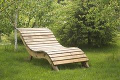 Banco de madeira envernizado do jardim no gramado Foto de Stock