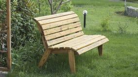 Banco de madeira envernizado do jardim no gramado Fotografia de Stock
