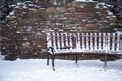 Banco de madeira perto de uma parede com neve Fotografia de Stock Royalty Free