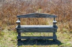 Banco de madeira resistido na grama de pradaria de Texas com luz solar da manhã fotografia de stock