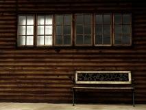 Banco de madeira solitário com Windows Fotografia de Stock