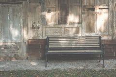banco de madera al lado de la casa de madera vieja Silla en parque relaje la forma de vida Fotografía de archivo