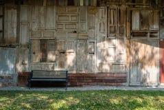 banco de madera al lado de la casa de madera vieja Silla en parque relaje la forma de vida Foto de archivo libre de regalías