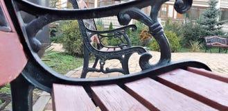 Banco de madera con las piernas del labrado-hierro en un parque de la ciudad Banco retro hermoso con las manijas del cordón del l foto de archivo libre de regalías