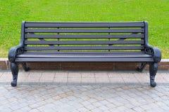 Banco de madera con las piernas negras adornadas del metal en un parque de la ciudad imagenes de archivo